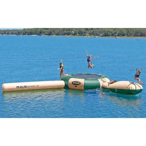 3 people playing on the Rave Aqua Jump 200 Water Park Northwoods edition.  There is a tan Aqua Log, a tan Aqua Launch, and the Rave Aqua Jump has alternating hunter green and tan panels.  The floating trampoline for lakes is in the middle of the lake.