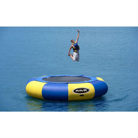 A man jumping and grabbing his feet on the yellow and blue Rave Aqua Jump Eclipse 150 Water Trampoline on a lake.
