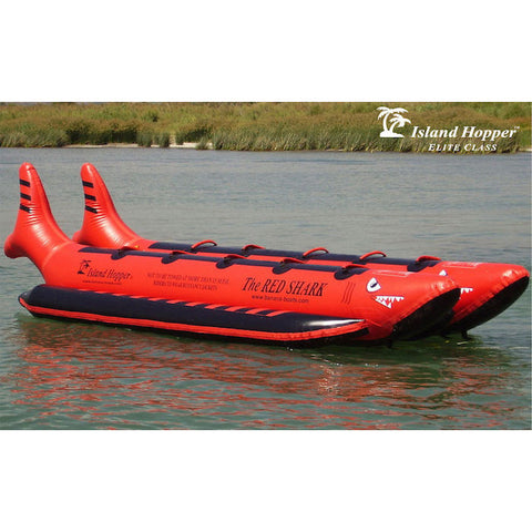 Side view of the Island Hopper 10 Person Red Shark Banana Boat sitting unoccupied on the lake.