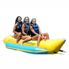 3 girls riding a yellow Island Hopper 3 Person Banana Boat Tube with light blue inflatable foot rests. On a white background.