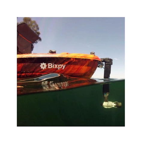 Bixpy Jet Thruster is used with a Bixpy Universal Rudder Adapter on an orange kayak.  The view is partially underwater and you can see the side view of the light grey, almost white Bixpy Jet Thruster.