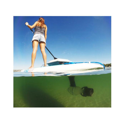 Bixpy Thruster Jet Motor is being used as a SUP motor and is viewed from a half underwater view.  There is a young woman standing on the paddle board with a paddle.  You can see the Bixpy Thruster underwater attached to a SUP Adapter.  The Bixpy Power Pack is on top of the SUP.