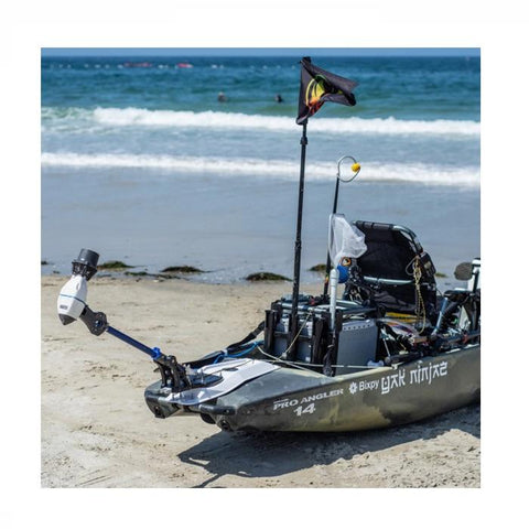 Bixpy Universal Power Pole Kayak Adapter  is shown in place on a kayak on the beach.  The motor is fully hinged and out of the water.