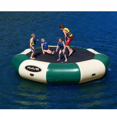 4 kids playing on a tan and green Rave Bongo 15 Water Bouncer Northwoods edition on the lake on calm dark blue water.
