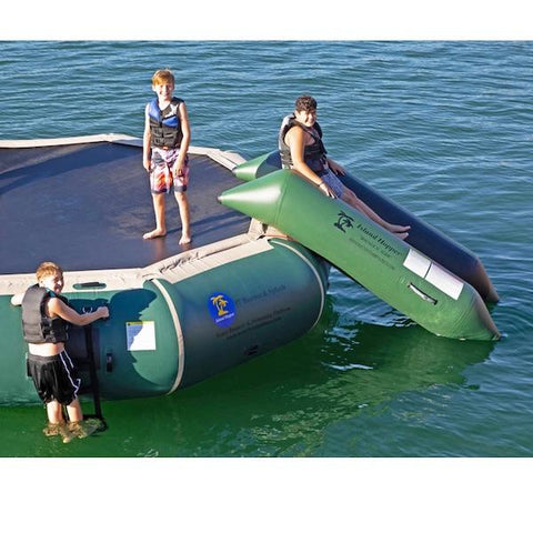 3 young boys getting ready to slide down the Island Hopper Bounce N Slide Inflatable Water Bouncer Slide. It is natural green and blends in nicely with the blue green water.
