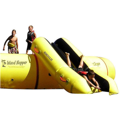 Island Hopper Bounce N Slide Attachment front view of one kid sliding down and two on the water trampoline next up to slide down the water slide.