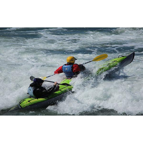 Green Advanced Elements AdvancedFrame Convertible Inflatable Kayak going through whitewater rapids.