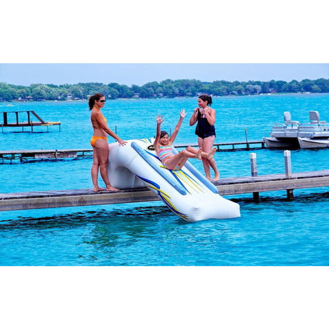 Young girl sliding down a Rave Inflatable Dock Slide while 2 adults stand by and watch here slide into the lake from the dock.