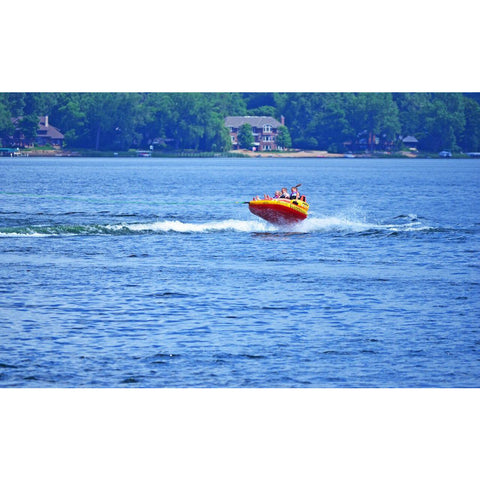RAVE #Epic 3 Person Towable Boat Tube flying over a wave out on the lake.