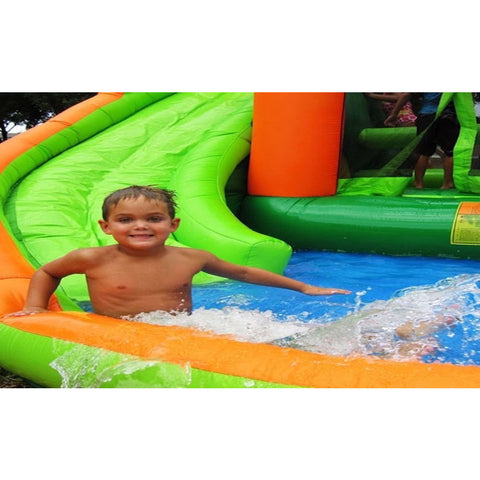 KidWise Endless Fun 11 in 1 Inflatable Bounce House and Water Slide boy arriving in splash pool from the green slide.