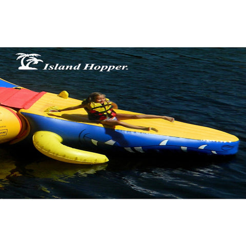 A young boy sliding down the tail attachment slide of the Island Hopper 15' Gator Monster Water Trampoline Water Park