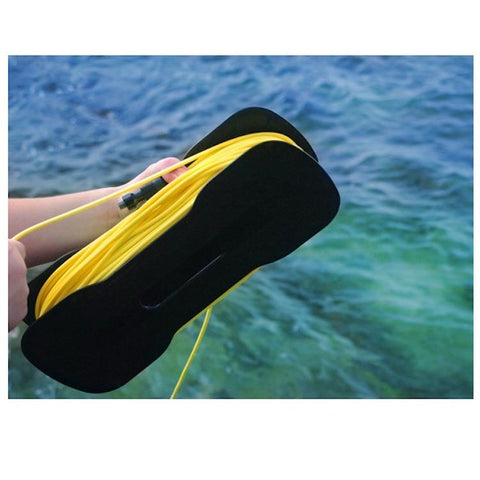 The yellow tether of the Chasing Gladius Mini Underwater Drone is wrapped around a black piece to store the tether.  A boy is holding it over the water, close up view.