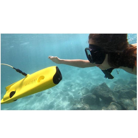Close up view of a snorkeler swimming up to the front and looking in the camera of the yellow Chasing Gladius Mini Underwater Drone.  The little girl is waving and reaching out to touch the top edge, the water is clear and light blue.