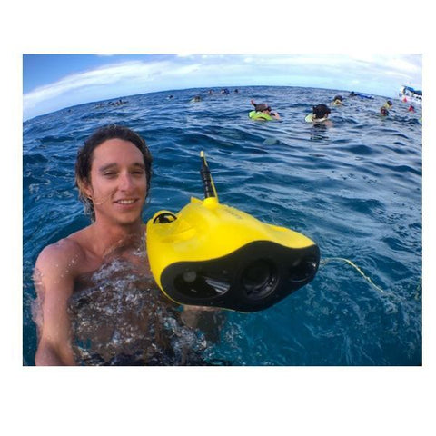 Young man holds a Chasing Gladius Mini Underwater Drone just above the surface of the water.  The yellow underwater drone for sale pops against the blue ski and dark blue water.