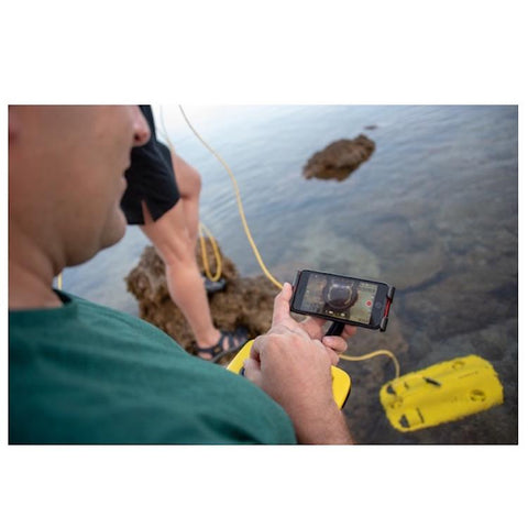 A man uses his phone to control the Chasing Gladius Mini Underwater Drone out at sea.  The Gladius Underwater drone for sale is on the surface of the water.
