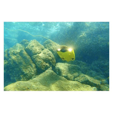 Underwater view of the Chasing Gladius Mini Underwater Drone with its LED Lights on and facing upward at a 45 degree angle.  The yellow Gladius Underwater Drone is near a light brown reef and the water is clear.