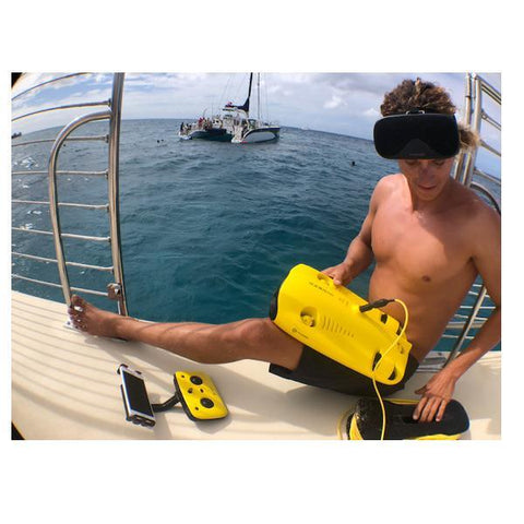 A young boy uses a Chasing Gladius Mini Underwater Drone from the side of a boat.  The yellow underwater drone for sale and remote control are nearby.