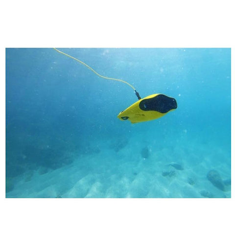 Chasing Gladius Mini Underwater Drone is underwater exploring through crystal clear blue water.  The underwater drone for sale is yellow with grey front side.