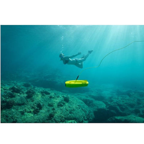 Chasing Gladius Mini Underwater Drone explores near the ocean floor while a scuba diver is nearby in the background.  The water is blue and clear and the yellow Gladius Under Water Drone is clearly visible.