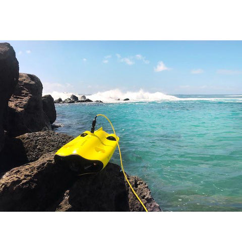 Chasing Gladius Mini Underwater Drone sits on a large rock next to the ocean as waves crash in the background.  You can see the details of the yellow underwater drone for sale and the yellow tether coming out of the black connector to the underwater drones for sale.