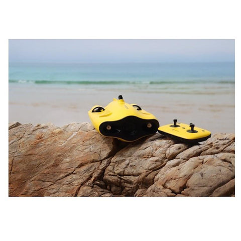 A Chasing Gladius Mini Underwater Drone with the Remote Control sit on a rock on the beach.  The underwater drone for sale is yellow as is the remote control with joysticks.