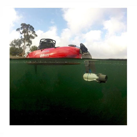 Bixpy Hobie Twist & Stow Kayak Rudder Adapter shown attached to the back of a red Hobie kayak floating in a lake.  Split shot camera angle shows the black Hobie Twist & Stow attached to the grey and black Jet Motor underwater.