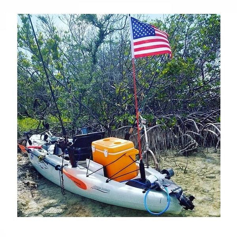 View of a kayak on the beach with an orange cooler and American flag upright 5 feet tall.  Bixpy Hobie Twist & Stow Kayak Rudder Adapter is attached and folded onto the back of the kayak.