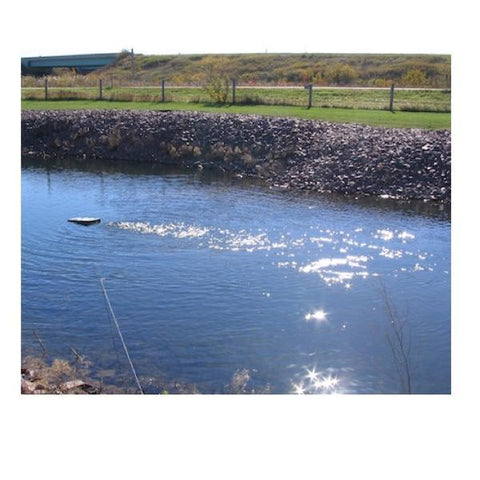 A Kasco De Icer Horizontal Float is in use in a pond and you can see the ripples in the water from the circulation.