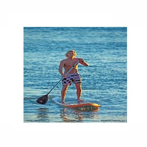 Man out paddling the orange and white Advanced Elements Hula 11 Inflatable SUP out on the ocean.
