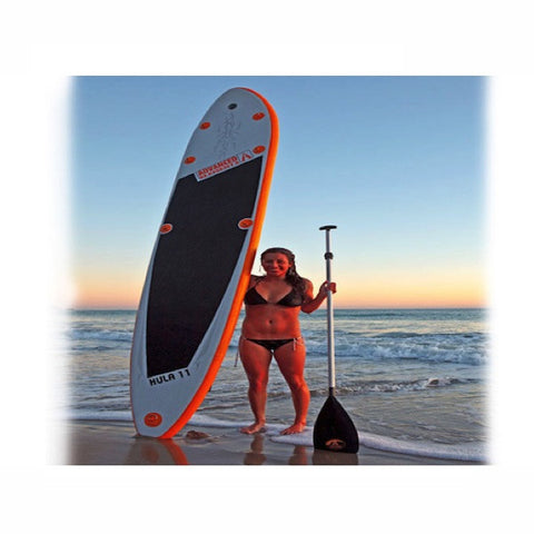 Advanced Elements Hula 11 Inflatable SUP.  Girl standing next to it with a paddle in one hand, iSUP in the other, beach in the background.