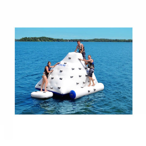 3 young adults climbing on a white Rave Floating Inflatable Iceberg 7 on a lake against a blue sky.