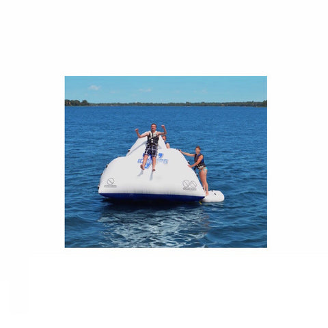 Guy sliding down a white Rave Floating Inflatable Iceberg 7 in the middle of the lake.