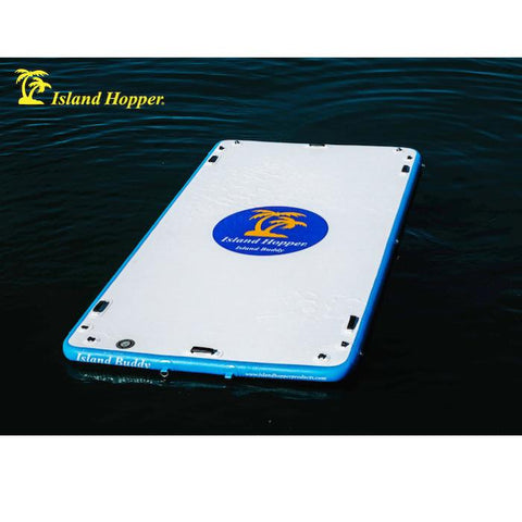 Island Hopper 12ft Island Buddy Inflatable Water Mat sitting in the middle of the lake by itself. It is white on top with a royal blue oval. Inside the oval is yellow palm trees and white Island Hopper Island Buddy lettering in the oval and on the sides.
