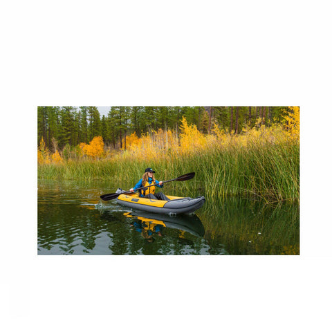 Yellow and Gray Advanced Elements Island Voyage 2 Inflatable Kayak being paddled down an easy river.