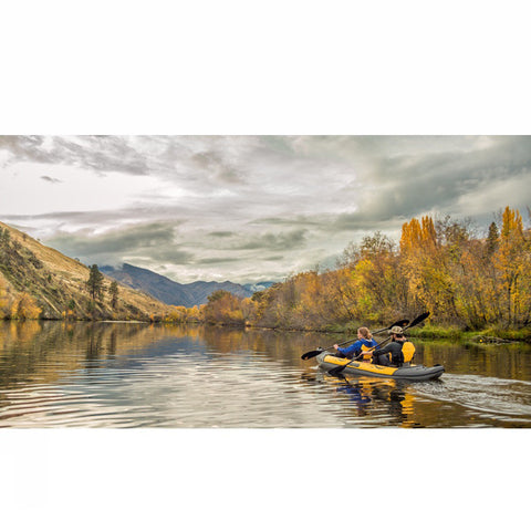 Man and woman paddling the yellow and grey Advanced Elements Island Voyage 2 Tandem Inflatable Kayak down a river in a picturesque scene.