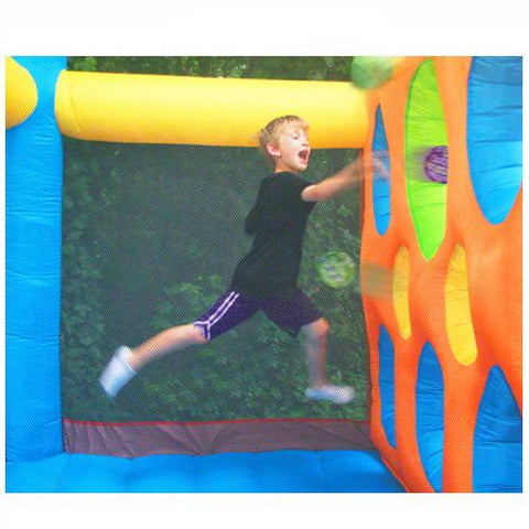 KidWise Jump'n Dodgeball Sports Bounce House in action dodgeball game.  Young boy jumping and throwing a neoprene ball through the openings in the inflatable partitioned wall.