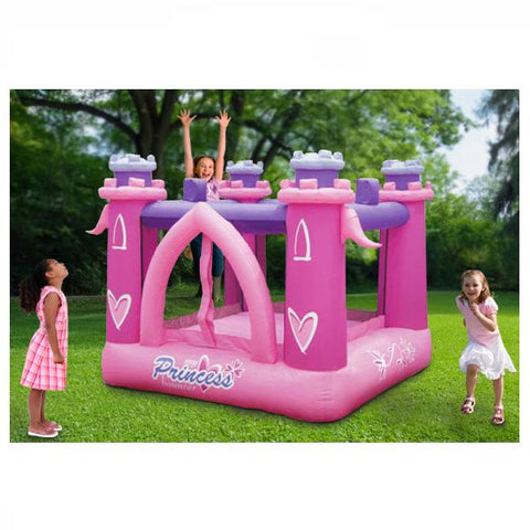 KidWise My Little Princess Bounce House outside in the backyard with 3 girls playing in and around the inflatable bounce house.  Pink and purple color scheme on the castle design.
