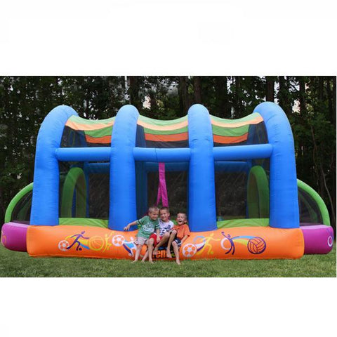 KidWise Arc Arena II Inflatable Sports Bounce House side view of the blue, orange, pink, and green color scheme with 3 kids sitting on the edge.  Nestled against a forest.