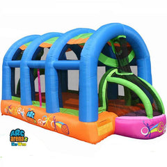 KidWise Arc Arena II Inflatable Sports Bounce House display image. The outside of the lower perimeter is orange and there are 4 inflatable blue supports that go over the top.  Soccer goal is visible with pink outer edge and lime green supports.