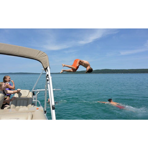 A teenager does a front flip off of the Lillipad Diving Board pontoon diving board.