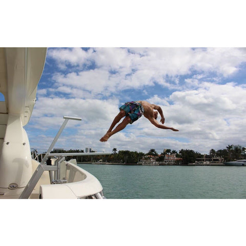 A teenager does a front flip off of the Lillipad Boat Diving Board