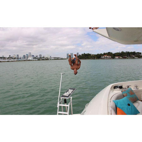 A teenager does a front flip off of the Lillipad Diving Board - Surface Mount mounted on the side of a boat out in the bay.  Also known as Lily Pad Diving Board