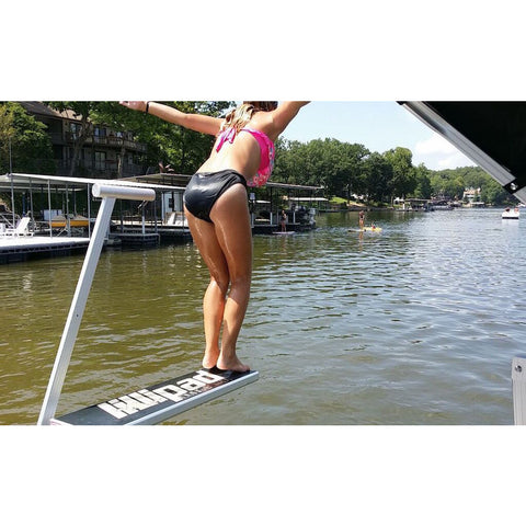 A girl jumping off of a pontoon boat diving board, Lillipad Diving Board into a lake.