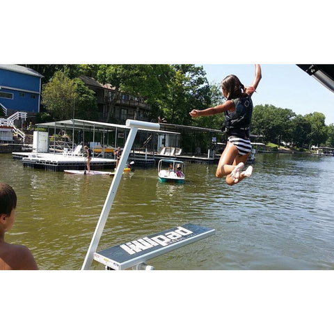 A young girl jumping off of a Lillipad Diving Board into a lake off of the pontoon diving board.  Also known as Lily Pad Diving Board