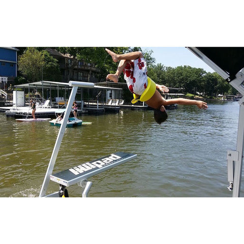 A young boy jumping off of a Lillipad Boat Diving Board into a lake.