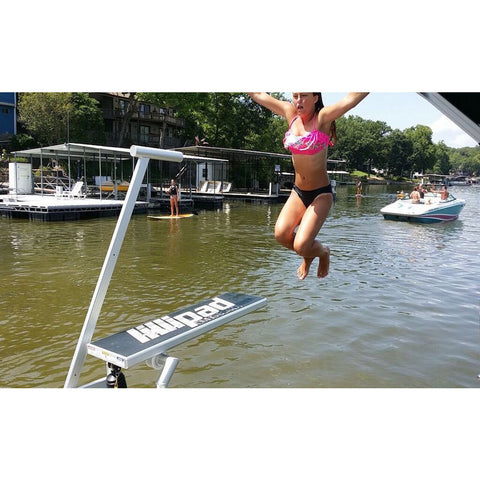 A young girl jumps off the lillipad boat diving board backwards into the lake while a boat passes in the background.