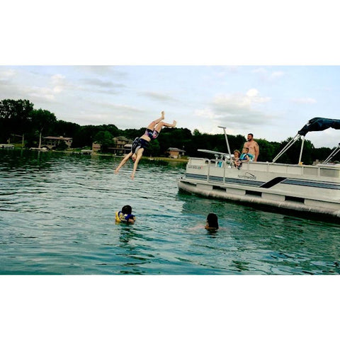Kids jumping off of the Lillipad Boat Diving Board in to the lake off of a pontoon boat.