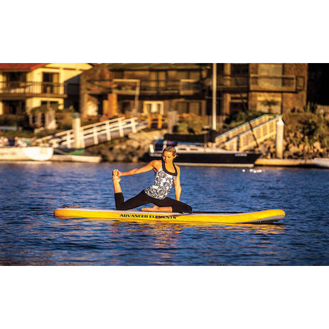 Woman doing yoga on the orange and white Advanced Elements Lotus Inflatable YSUP out on the water.