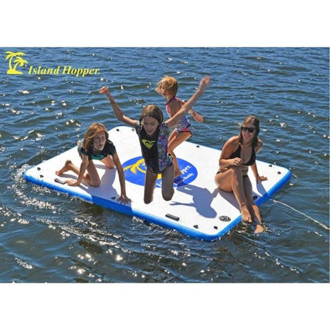 Island Hopper Island Buddy Inflatable Floating swim platform is being used by 4 kids jumping off of it into the lake.  The inflatable water platform has a white top with blue circle in the middle.  The Island Hopper floating swim platform is floating attached only by a rope, water surrounds the floating swim platform.