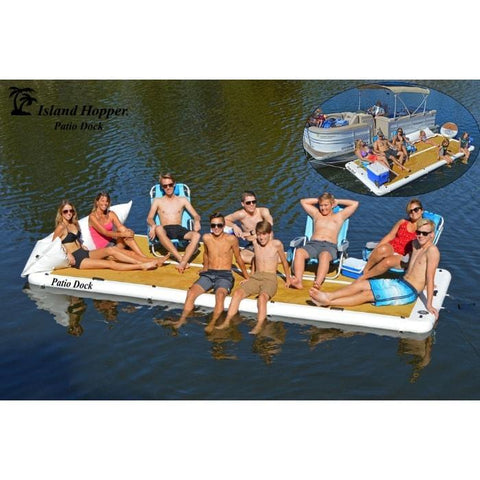 Island Hopper Patio Dock Floating Swim Platform Inflatable Dock is shown in the middle of a lake with 10 people on board.  The inflatable dock is remaining perfectly buoyant and some of the people are sitting while others are in chairs. In the background there is another Island Hopper Inflatable Dock up against a pontoon.